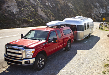 Auto Plus Insurance Group LLC | Red truck parked on the side of a road near a mountain with a silver RV attached to the back and a luggage rack on top