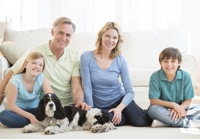 Auto Plus Insurance Group LLC | A family sitting on their living room floor in front of a couch smiling with their dog